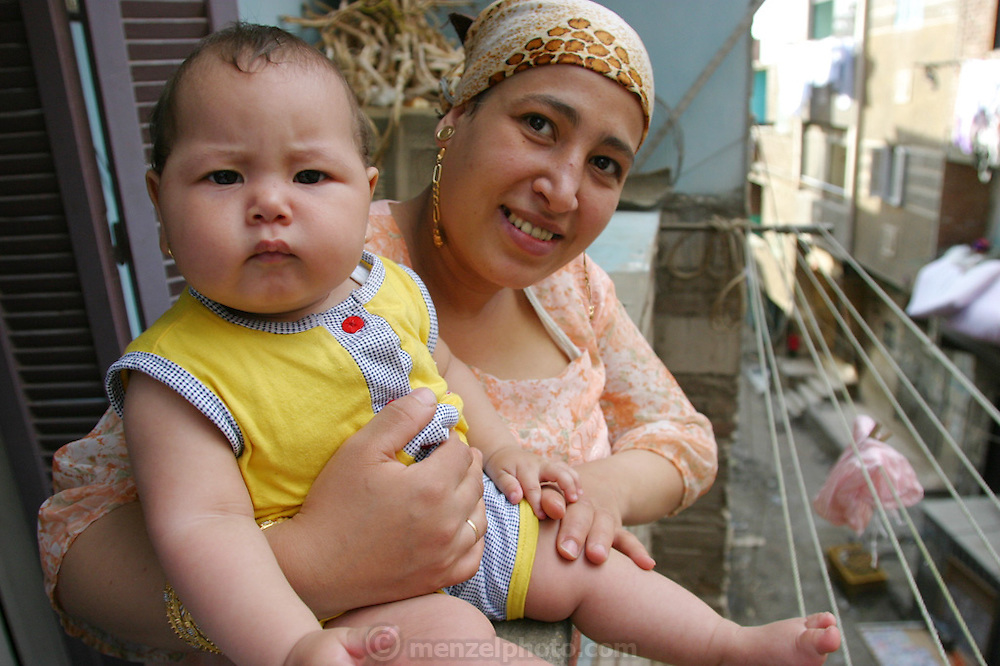 (MODEL RELEASED IMAGE). Nadia Mohamed Ahmed, 36, holding her baby Nancy, 8 months on the fourth floor balcony of their apartment in the old part of Islamic Cairo, Egypt. (Supporting image from the project Hungry Planet: What the World Eats.)