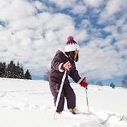 Little girl with skis in the snow