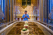 "22 JULY 2013 - PHRA PHUTTHABAT, THAILAND:  A man prays at the footprint of Buddha in the Mondop (chapel that houses the footprint) before the Tak Bat Dok Mai at Wat Phra Phutthabat in Saraburi province of Thailand, Monday, July 22. Wat Phra Phutthabat is famous for the way it marks the beginning of Vassa, the three-month annual retreat observed by Theravada monks and nuns. The temple is highly revered in Thailand because it houses a footstep of the Buddha. On the first day of Vassa (or Buddhist Lent) people come to the temple to ""make merit"" and present the monks there with dancing lady ginger flowers, which only bloom in the weeks leading up Vassa. They also present monks with candles and wash their feet. During Vassa, monks and nuns remain inside monasteries and temple grounds, devoting their time to intensive meditation and study. Laypeople support the monastic sangha by bringing food, candles and other offerings to temples. Laypeople also often observe Vassa by giving up something, such as smoking or eating meat. For this reason, westerners sometimes call Vassa the ""Buddhist Lent.""    PHOTO BY JACK KURTZ"