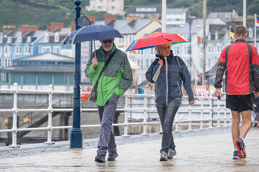 ©Licensed to London News Pictures. 30/07/2019. Aberystwyth, UK. Holidaymakers  in their raincoats and umbrellas walking along the promenade in Aberystwyth in the rain as a belt of thundery and very wet weather spreads across much of the central parts of the UK, bringing with it the risk of disruptive flooding and treacherous driving conditions. Photo credit : Keith Morris/LNP