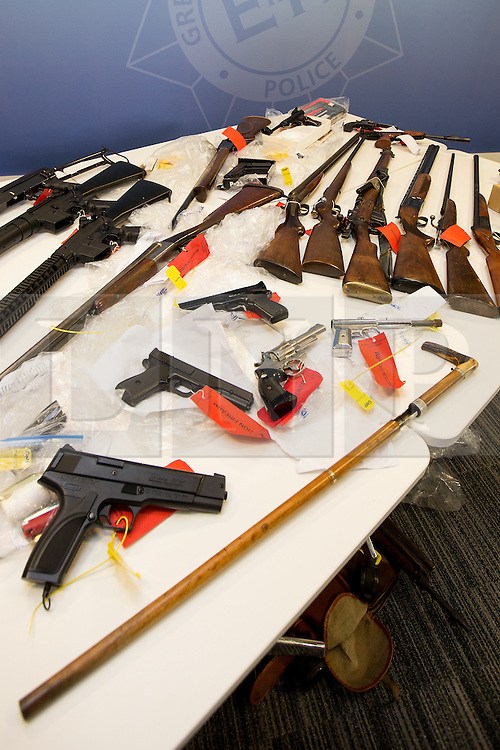 © Licensed to London News Pictures . 07/08/2014 . Manchester , UK . A shotgun that fires live ammunition , disguised as a walking stick , amongst the haul . Greater Manchester Police displays some of the cache of firearms and ammunition they collected during a two week firearms amnesty in July , at the force's North Manchester headquarters , this morning (7th August 2014) . GMP reports collecting 225 firearms and over 3000 rounds of ammunition during the fortnight amnesty of which , they say, over 80 of the weapons were illegally owned . Amongst the haul were rifles, shotguns , handguns and air weapons as well as imitation and antique firearms . Photo credit : Joel Goodman/LNP