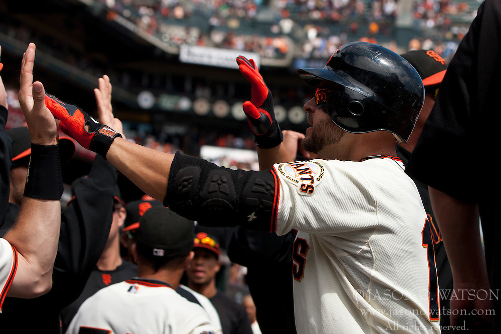 September 4, 2011; San Francisco, CA, USA;  San Francisco Giants left fielder Cody Ross (right) celebrates with teammates in the dugout after hitting a home run against the Arizona Diamondbacks during the first inning at AT&T Park.