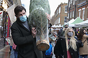 A man wearing a face mask carries a Christmas tree away in Columbia Road Flower Market on 6th of December 2020 in Hackney, London, United Kingdom. The flower market in East London is all year around for all kinds of plants and flowers but at Christmas time, many come to buy their Christmas tree and decorations for the festive season. The national lockdown 2 has just ended and London is under tier 2. The pandemic is still raging so many wear face masks, even outside, because of the lack of social distancing.
