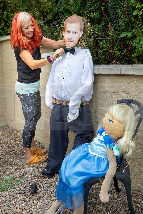 """© Licensed to London News Pictures. 27/08/2021. Desford, Leicestershire, UK. Desford Scarecrows. The Desford scarecrow festival takes place over the Bank Holiday weekend and this years theme is """"Books"""". The scarecrows have been hand made by local villagers to bring a smile to those passing through the Leicestershire village. They can be seen climbing through windows, taking lunch, singing songs, there is even a Prince Harry taking part in a Cinderella scene. Pictured, Jo Rowe adjusts Prince Harry's bowtie in a scene from Cinderella. Photo credit: Dave Warren / LNP"""