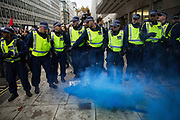 Metropolitan Police officers monitor a smoke grenade set off by students attending a National Demonstration for a Free Education on 4th November 2015 in London, United Kingdom. The demonstration was organised by the National Campaign Against Fees and Cuts NCAFC in protest against tuition fees and the Government's plans to axe maintenance grants from 2016.