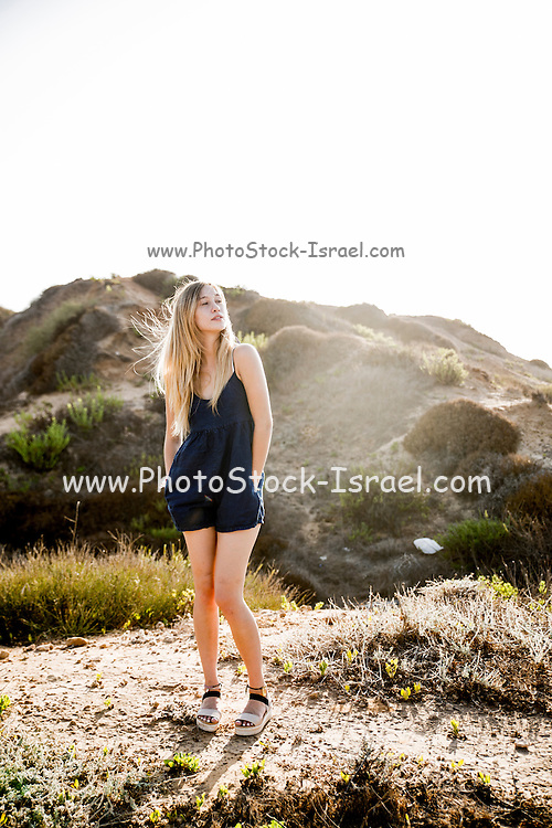 Young blond female model in casual clothes on a beach. Model released