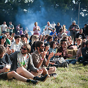 Audience listens to live music in the late sun on a hot summers day at Super Normal art festival in Oxfordshire on the land of the Braziers Park. The festival is a mix of live music and performance art.