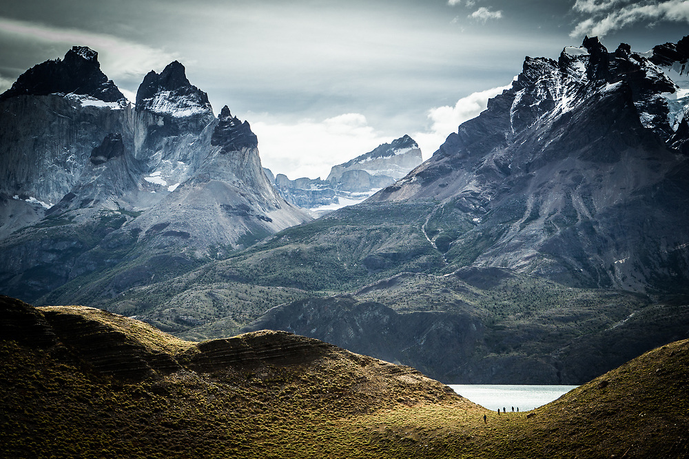 Group of adventurers hiking in the distance with a big mountain range behind them in Torres del Paine National Park, Chile.