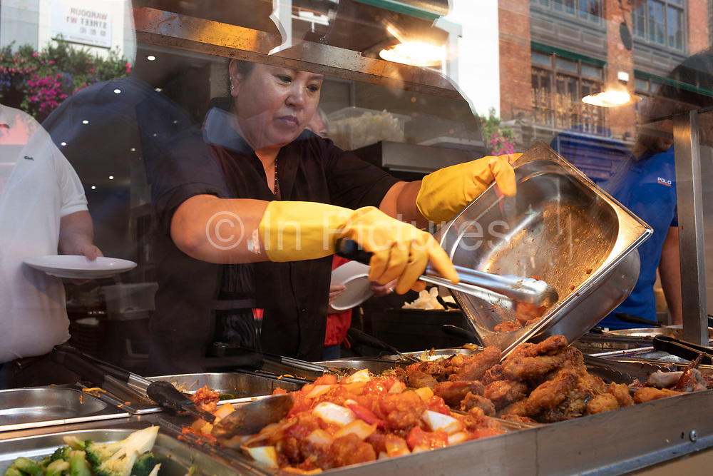 Woman serving out chicken at an eat as much as you like hot buffet at a Chinese restaurant in Chinatown in London, England, United Kingdom. Many people eat bargain food responsibly and it provides great value for consumers, however concerns over obesity levels in the UK remain, especially with foods containing high levels of fat and sugar. Obesity is a medical condition in which excess body fat has accumulated to the extent that it may have a negative effect on health.