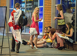 © Licensed to London News Pictures . 15/06/2014 . Manchester , UK . A man wearing an England flag walks passed several women eating takeaways . People on a night out in Manchester City Centre overnight , following England's defeat to Italy in the World Cup . Photo credit : Joel Goodman/LNP