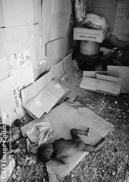 A three-year-old child sleeps on a cardboard box in Cite Carton, city of carton s.  Her father has never held a regular job, and makes little money working odd jobs when he can find them. Cite Carton is the most poverty-stricken part of C ite Soleil, the poorest section in the poorest city of the Western hemisphere. The cardboar d shacks of Cite Carton are built on a landfill and have no running water or el ectricity. The inhabitants sink up to their ankles in human and animal waste wh en it rai ns, and the nauseating sewage ponds throughout the slum contribute to the nation's sanitation-related diseases.