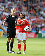Joe Allen of Wales gets a talking to from referee Martin Atkinson. UEFA Euro 2016, last 16 , Wales v Northern Ireland at the Parc des Princes in Paris, France on Saturday 25th June 2016, pic by  Andrew Orchard, Andrew Orchard sports photography.