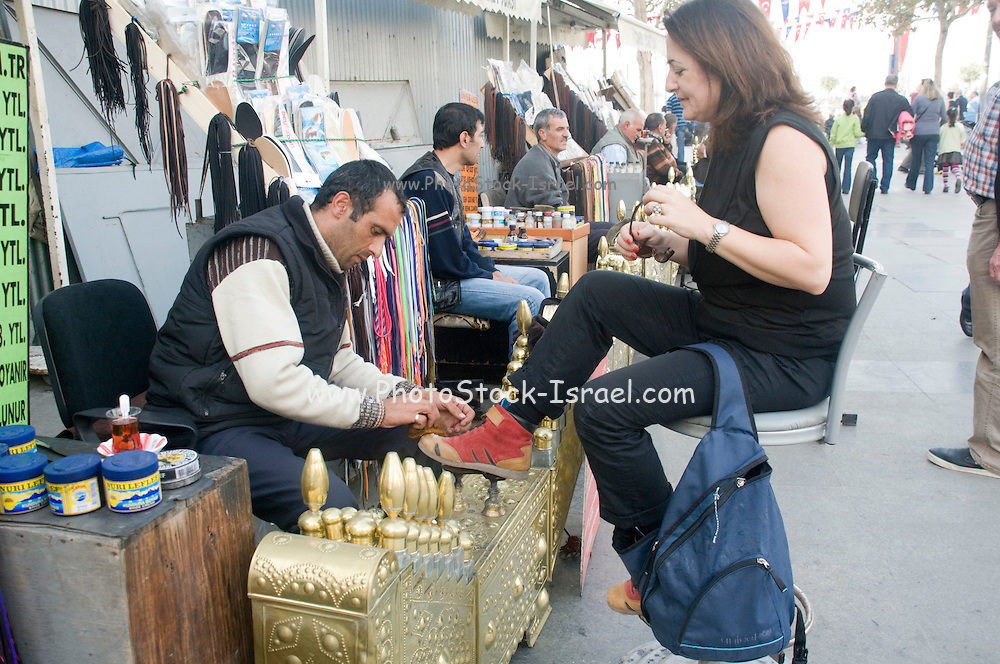 Turkey, Istanbul, Shoeshine stand female client having her shoes polished