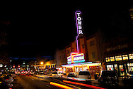 The Tower Theater in downtown Bend, Oregon at night with a glowing neon sign.