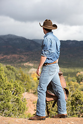 rugged cowboy with a saddle looking at a mountain range