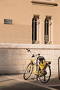 Yellow bicycle for rent on street side, Grenoble, France