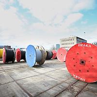 Nederland, Amsterdam , 16 april 2010..Draka is een Nederlands beursgenoteerde onderneming actief in de kabelindustrie..Draka ontwikkelt, produceert en verkoopt kabels en kabelsystemen. Deze kabels worden toegepast voor communicatiedoeleinden (zoals glasvezelkabel) maar ook worden de producten toegepast in onder meer de auto-industrie en liftsystemen. Draka's activiteiten zijn onderverdeeld in drie groepen: Energy & Infrastucture, Industry & Specialty en Communications..Draka bestaat 100 jaar..op de foto enkele katrollen kabel op de vestiging in Amsterdam noord wachten op transport.Foto:Jean-Pierre Jans