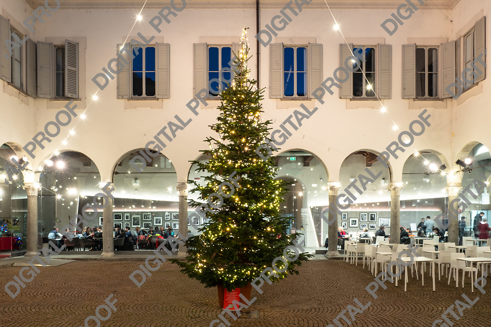 Arched building with open air cafe and relaxing people on decorated Via Dante street on Christmas Eve in Milan Italy