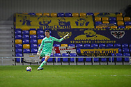 AFC Wimbledon goalkeeper Nikola Tzanev (13) passing ball up pitch in front of AFC Wimbledon banners during the EFL Trophy match between AFC Wimbledon and U21 Arsenal at Plough Lane, London, United Kingdom on 8 December 2020.
