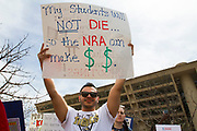 A teacher holds a sign protesting the current spate of school shootings that have plagued the US, during the March for Our Lives event in front of Dallas City Hall on Saturday.
