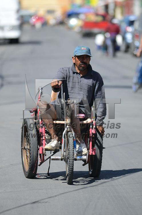 Toluca, México (Octubre 22, 2016).- Con un triciclo modificado para operarlo con sus manos, un hombre con capacidades diferentes se gana la vida recolentando Pet y cartón por las calles de la capital mexiquense. Agencia MVT / Arturo Hernández.