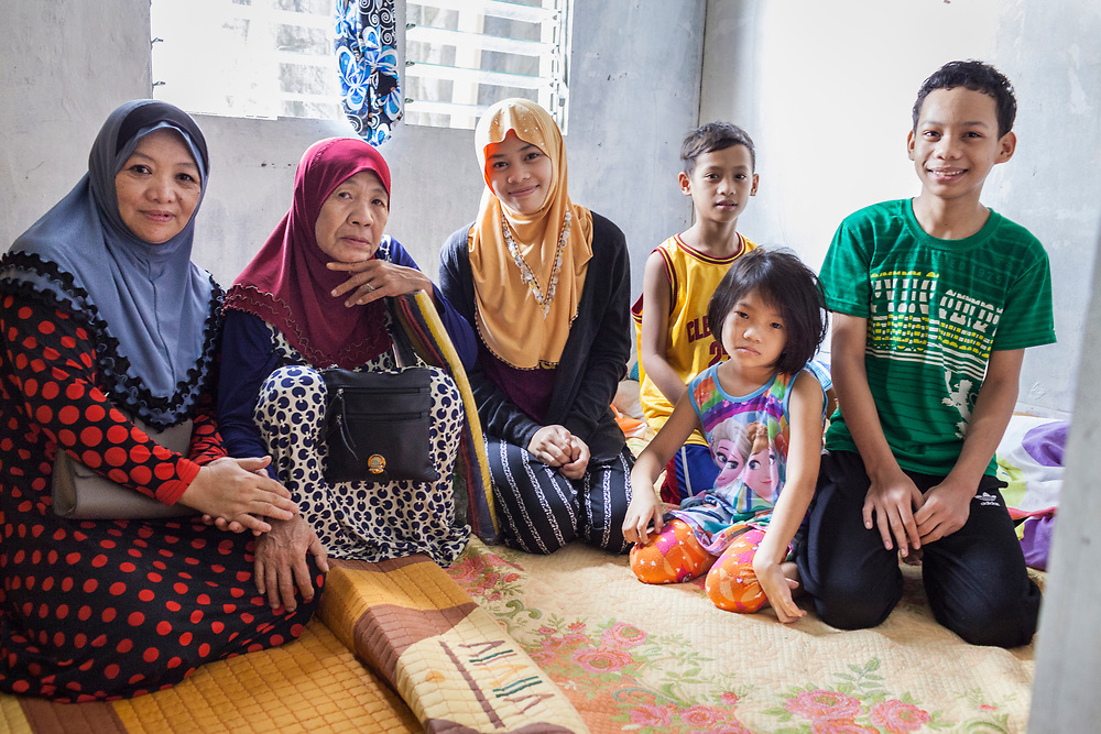 Davao City, Mindanao, Philippines - JUNE 22: A portrait of Azisah Rimbang and her family.  Azisah and 7 members of her family fled Marawi after the ISIS backed Maute Group has sieged the city. They found refuge in a house that she shared with 30 other people in the Mini Forest Barangay 23C. Currently, over 570 families and roughly 2500 evacuees from Marawi reside in the area.