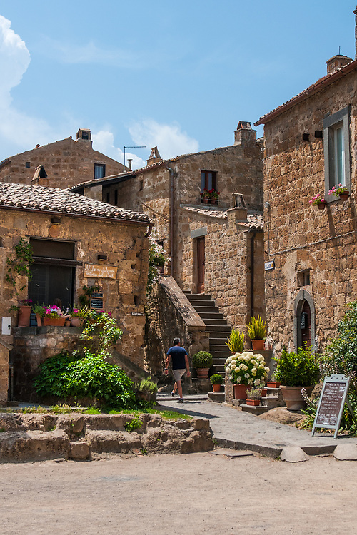 """A man walks in the streets of the village of Civita di Bagnoregio.<br /> Civita di Bagnoregio is a town in the Province of Viterbo in central Italy, a suburb of the comune of Bagnoregio, 1 kilometre (0.6 mi) east from it. It is about 120 kilometres (75 mi) north of Rome. Civita was founded by Etruscans more than 2,500 years ago. Bagnoregio continues as a small but prosperous town, while Civita became known in Italian as La città che muore (""""The Dying Town""""). Civita has only recently been experiencing a tourist revival. The population today varies from about 7 people in winter to more than 100 in summer.The town was placed on the World Monuments Fund's 2006 Watch List of the 100 Most Endangered Sites, because of threats it faces from erosion and unregulated tourism."""