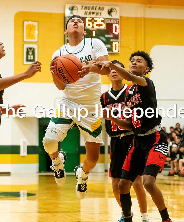 Photo - Jeffery Jones<br /> <br /> Thoreau Hawk Cordell Platero (3) jumps on his way the basket and gets past Crownpoint Eagle Corey Bell Jr. (2) during Friday night's game at Thoreau High School