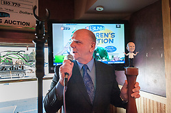 Children's Christmas Auction founder Warren Bailey holds the Pub Mania sceptor, complete with a bobblehead likeness of himself, as he makes comments prior to the start of the annual funraising event at Patrick's Pub and Eatery in Gilford on Thursday, December 6, 2012.  (Alan MacRae/for the Laconia Daily Sun)