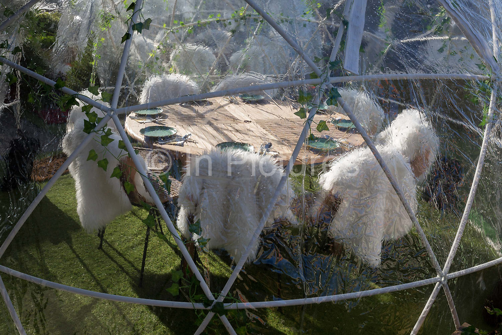 Places are set for customers inside a geodesic dome of an outdoor restaurant on the Thames waterfront at Kingston, on 7th November 2019, in London, England. A geodesic dome is a hemispherical thin-shell structure lattice-shell based on a geodesic polyhedron.