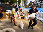 "30 DECEMBER 2013 - BANGKOK, THAILAND:   Anti-government protestors fortify their positions by placing sandbags across Ratchadamnoen Road in Bangkok. Violence around the anti-government protest sites has escalated in recent days and several protestors have been hurt by small explosive devices thrown at their guard posts. As a result, protestors are fortifying their positions with sandbags and bunkers. Suthep Thaugsuban, the leader of the anti-government protests in Bangkok, has called for a new series of massive protests after the 1st of the year and said it the shutdown, or what he described was the seizure of the capital, would be the day when ""People's Revolution"" would ""begin to end and uproot the Thaksin regime.""        PHOTO BY JACK KURTZ"