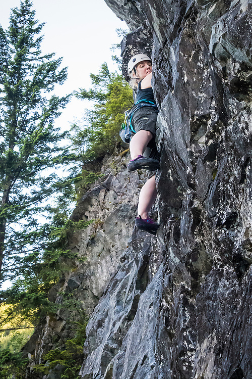 Looking up at a woman rock climbing on a top rope at Exit 38 in the central Washington Cascade mountains, Washington State, USA.