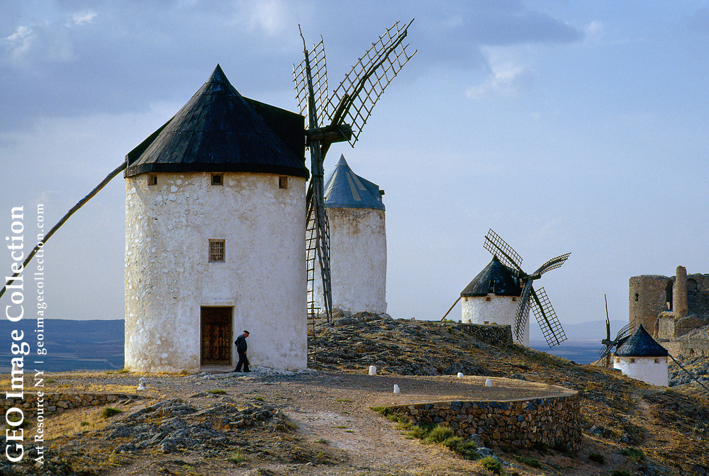 Four old whitewashed windmills sit atop a rise over the plains; their arms are warped with disrepair, and although they no longer work, they serve as monument s to the past.