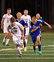 Hopkinton's Owen Kanter and Gilford's Codi Sanborn charge the ball during NHIAA Division III semi final Tournament game Wednesday evening at LHS turf field.  (Karen Bobotas/for the Laconia Daily Sun)