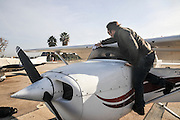 Pilot perform a preflight check on a cessna skyhawk