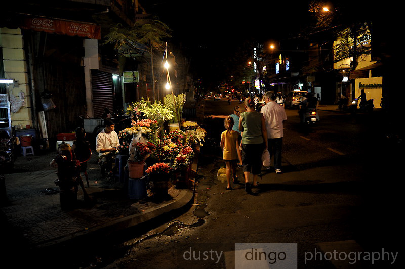 Man selling flowers from roadside stall, with western family walking past.<br /> Ho Chi Minh City (Saigon), Vietnam