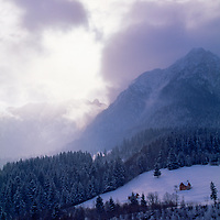 A winter storm clears over a farmhouse and the Transylvanian Alps.