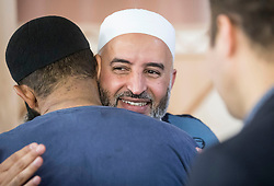 Imam Dr Mohammed Taher hugs a worshipper following the Eid prayer the Eid prayer, which marks the end of Ramadan and the start of Eid, at Leeds Grand Mosque in Yorkshire.