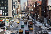 Yellow Taxis and trucks drive along 10th Avenue in Chelsea, New York City, New York , United States of America.  The city has just experienced a record breaking snowstorm and the side of the streets are still covered in snow mounds.