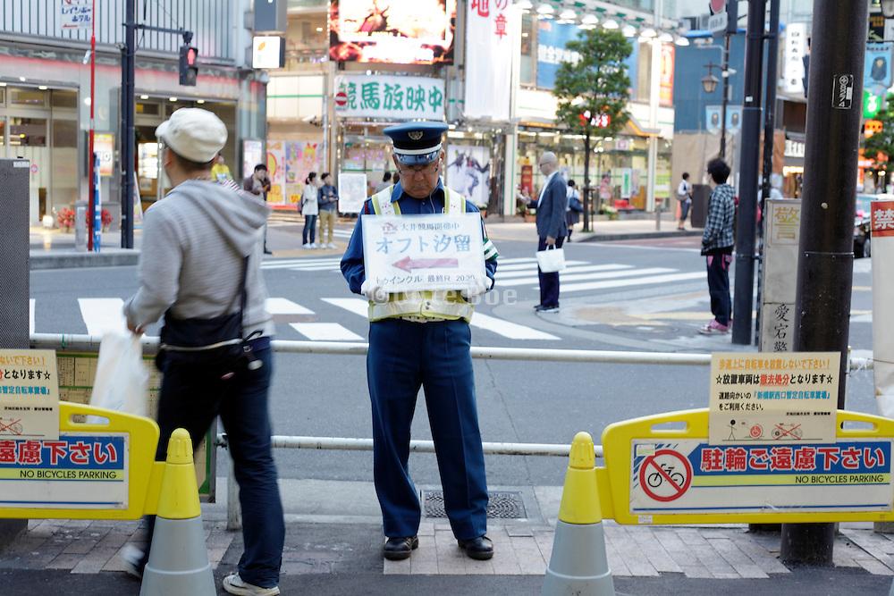 Shinbashi Tokyo man in uniform holding a sign up