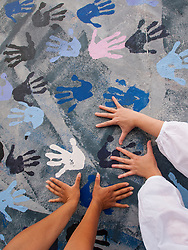 Tourists place hands on painted mural at Berlin Wall at East Side Gallery in Berlin, Germany