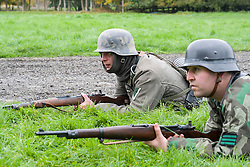 Re-enactors portrayiing German panzer grenadiers from the Großdeutschland Division. both are wearing the iconic Steel Helmet. The man on the left has a gefreiter rank badge on his arm. The soldier on the right is wearing a tactical rank badge of Feldwebel on his camouflage smock<br /> Pickering Showground battle reenactment 1940 war time weekend<br /> <br /> 17/18 October 2015<br />  Image © Paul David Drabble <br />  www.pauldaviddrabble.co.uk
