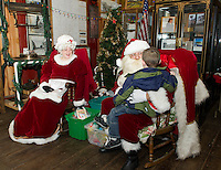 Mr. and Mrs. Claus listen intently as Brayden Day tells Santa what he would like for Christmas this year at the Lakeport Freight House Museum Saturday afternoon.  (Karen Bobotas/for the Laconia Daily Sun)