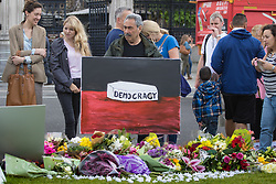 Parliament Square, Westminster, London, June 17th 2016. Following the murder of Jo Cox MP friends and members of the public lay flowers, light candles and leave notes of condolence and love in Parliament Square, opposite the House of Commons. PICTURED: Satirical painter Kaya Mar holds his sombre work as mourners place flowers in Parliaments Square.