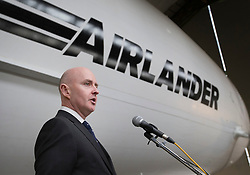 © Licensed to London News Pictures. 21/03/2016. Bedford, UK. Stephen McGlennan Chief Executive Officer of Airlander unveils the fully completed Airlander 10 hybrid airship at Cardington.  This is the largest aircraft currently flying. It uses innovative technology to combine the characteristics of fixed wing aircraft and helicopters with lighter-than-air technology to create a new breed of hyper-efficient aircraft. It can stay airborne for up to five days at a time if manned, and for over 2 weeks unmanned. It will fulfil a wide range of communication, cargo carrying and survey roles in both the military and commercial sectors all with a significantly lower carbon footprint than other forms of air transport. Photo credit: Peter Macdiarmid/LNP