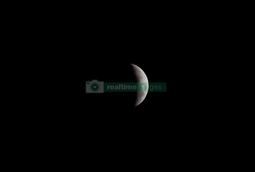 January 21, 2019 - London, London, United Kingdom - Super blood wolf moon. ..Super blood wolf moon seen in an early hour of Monday, from Sir Steve Redgrave Bridge in London...A total lunar eclipse occurs when the Earth passes exactly between the Sun and the Moon, creating a shadow which stops solar rays reaching the lunar surface..The red effect is due to Earth's atmosphere. Without an atmosphere the Moon would appear black or even totally invisible when it was within Earth's shadow. (Credit Image: © Gustavo Valiente/i-Images via ZUMA Press)