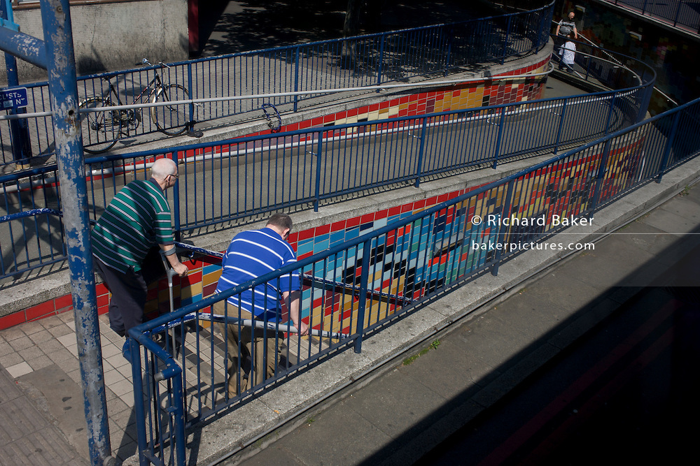 Two elderly men carefully descend steps into an inner-city underpass at Elephant & Castle, in central London.