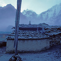 Fog creates a dusting of rime on stone buildings near Tengboche Monastery in Nepal's Himalaya.  Mounts Kangtega and Thamserku rise in the background.