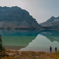 Photographers frame scenes beside Bow Lake in Banff National Park, Alberta, Canada. Mount Thompson & Portal Peak rise in the background.