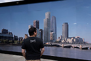 The rear view of a man who is looking at the image of the London skyline which is printed on a construction hoarding on the Southbank, on 10th June 2021, in London, England.